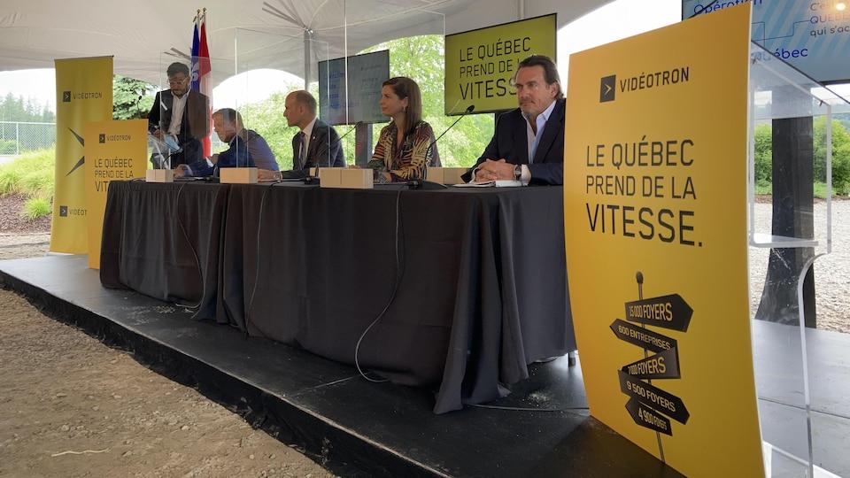 Les députés et Pierre Karl Péladeau assis à une table lors de l'annonce.