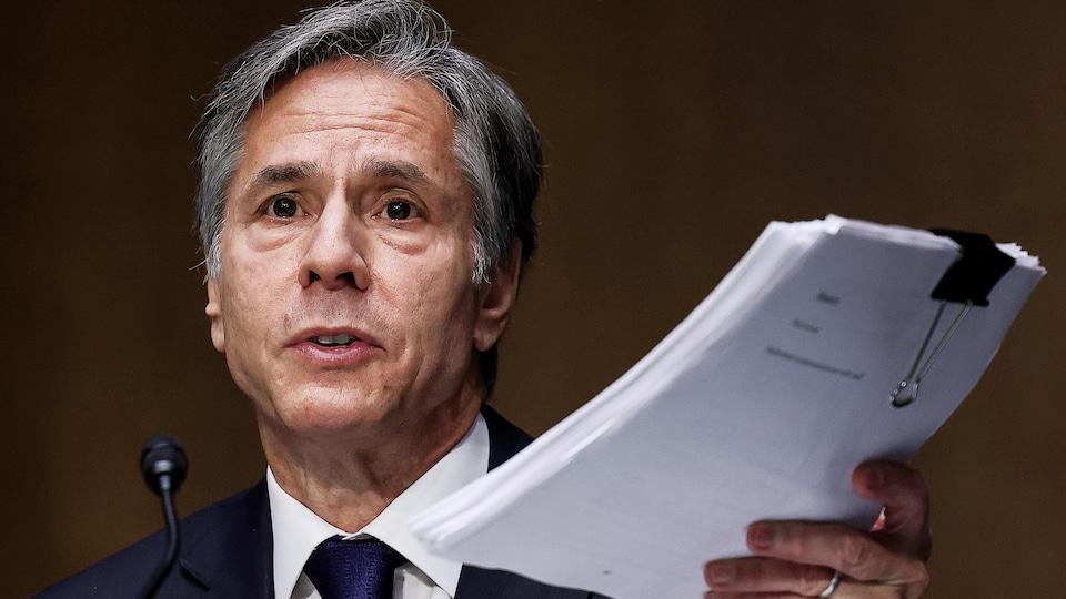 Antony Blinken, devant un micro, brandit un document épais.