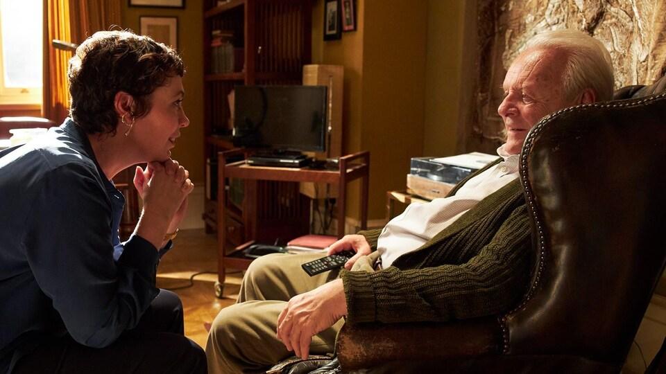 Une femme parle à un homme qui est assis dans un fauteuil.