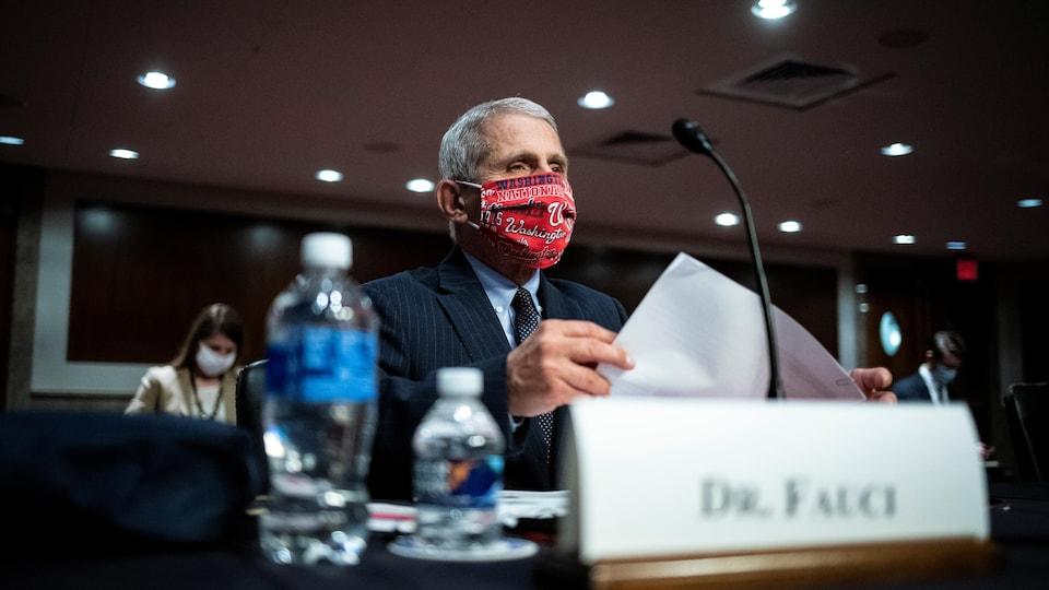 Portant un masque rouge, le Dr Fauci témoigne devant un comité du Sénat, des documents à la main, des bouteilles d'eau près de lui.