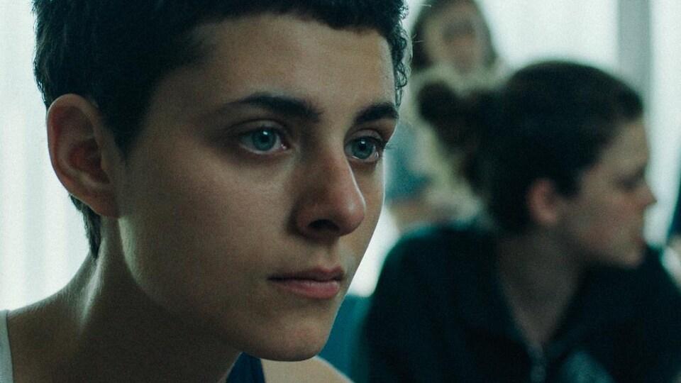 Une jeune femme regarde vers la droite.