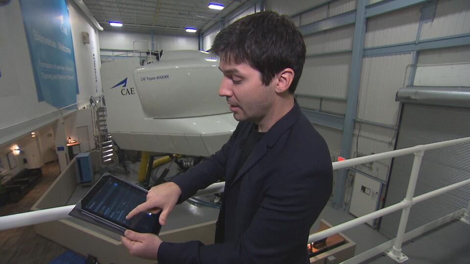 M. Dufour montre à l'aide d'une tablette l'utilisation d'un logiciel. Derrière-lui, on voit un simulateur de CAE.