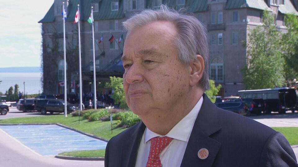 Gros plan sur le secrétaire général de l'ONU Antonio Guterres, avec le Chateau Frontenac en arrière-plan.