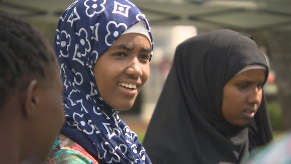 Une jeune fille souriante, en arrière-plan, une autre jeune fille, les deux portent le hijab.