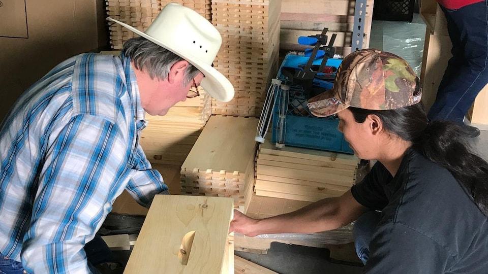 Ron Miksha tient les côté une boîte de bois et montre à Sharon comment les assembler.