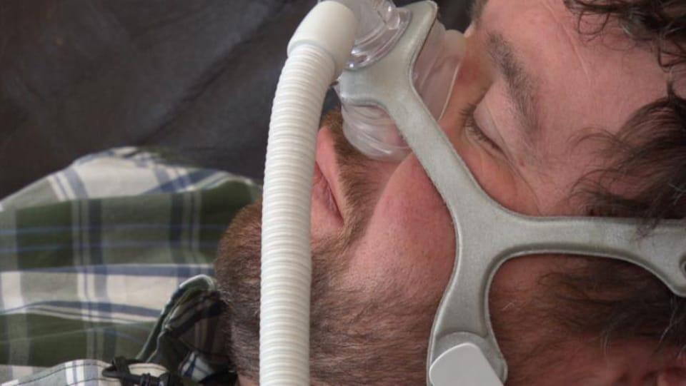Un homme dort en portant une machine CPAP contre l'apnée du sommeil.