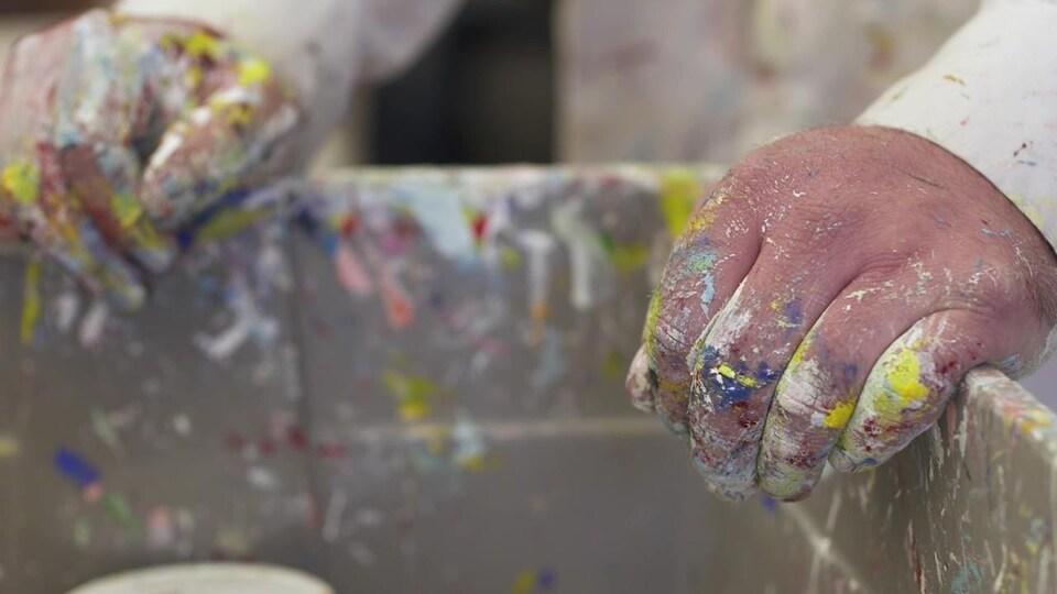 Des mains d'artistes, couvertes de peinture.