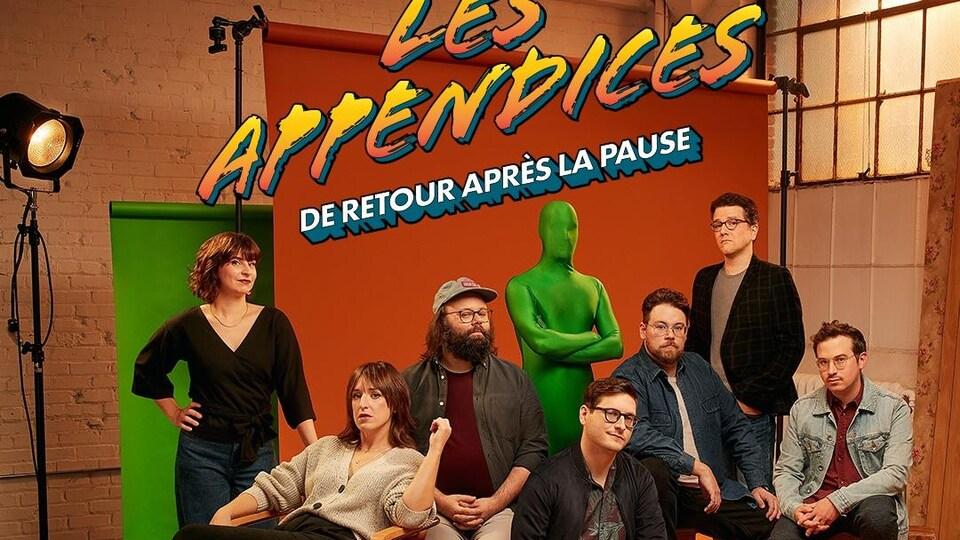 Quatre hommes et deux femmes posent à côté d'une personne habillée d'une combinaison verte de la tête aux pieds.