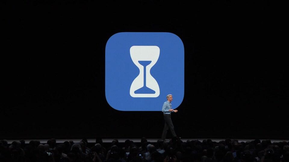 Une capture d'écran de la présentation montrant le logo de l'application Screen Time (un sablier dans un carré bleu aux coins arrondis) derrière un présentateur sur la scène.