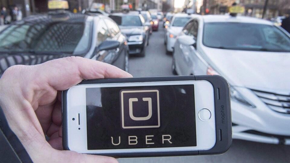 Un téléphone dans la main d'un passant dont l'écran affiche le logo d'Uber.