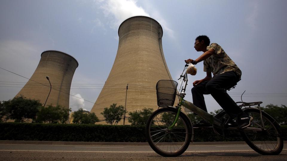 Un homme passe à vélo devant deux grandes cheminées d'où sort une fumée polluée.