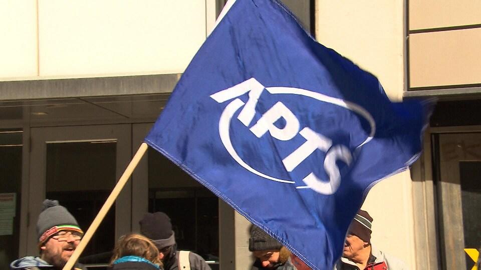 Un manifestant avec un drapeau de l'APTS.