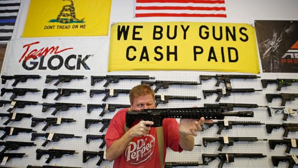 Un homme tient une arme à feu dans un magasin.