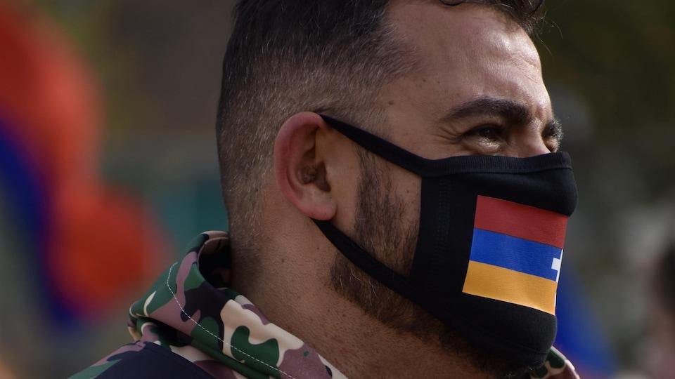 Un homme avec un drapeau de la République du Haut-Karabakh sur son masque.