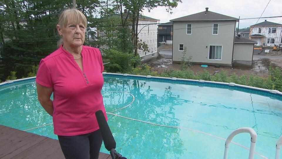 Une femme en bordure d'une piscine rpond aux questions d'un journaliste.
