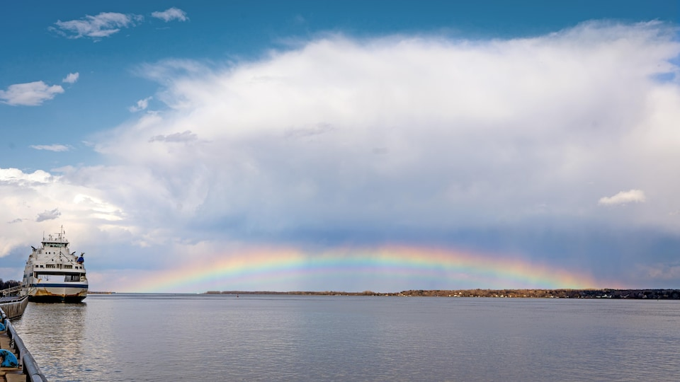 Un arc-en-ciel surplombe le fleuve.