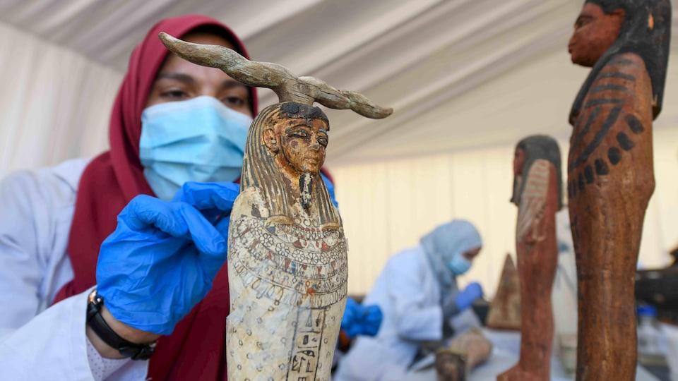 Une archéologue masquée nettoyant une statuette.