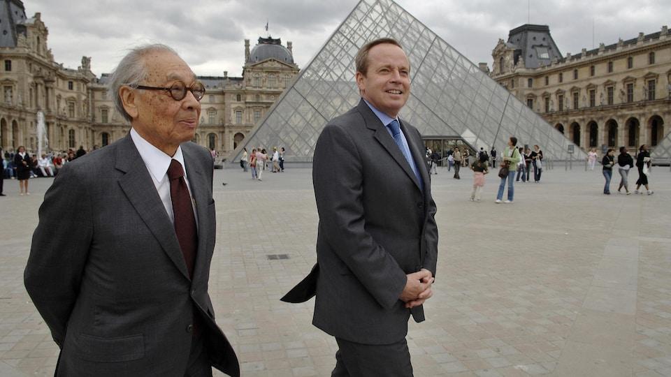 L'architecte Ieoh Ming Pei et le ministre français de la Culture Renaud Donnedieu de Vabres marchent dans la cour Napoléon du musée du Louvre.