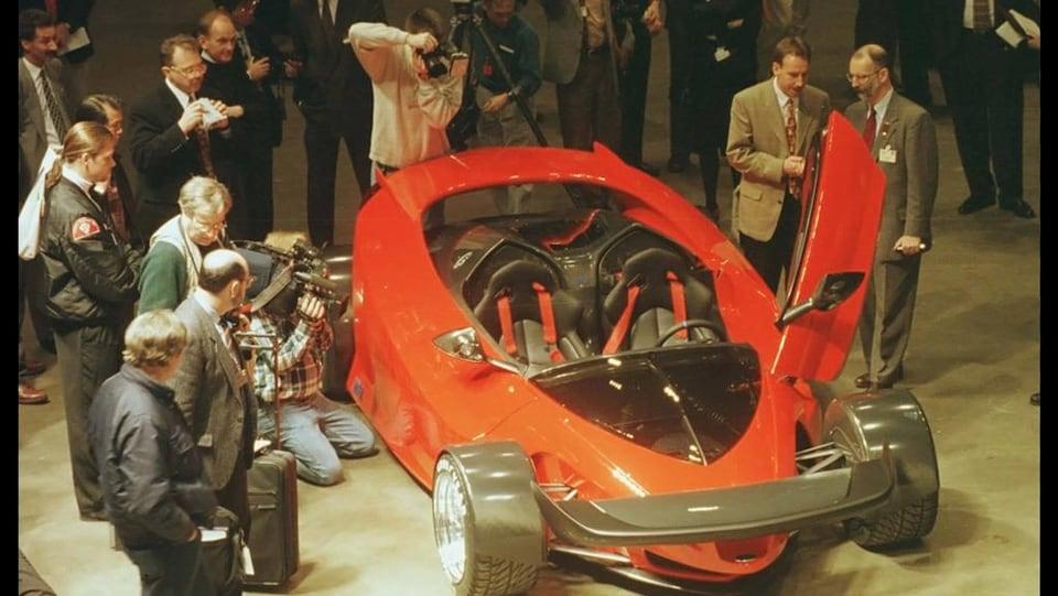 Une voiture de sport rouge-orangée dont les lignes rappellent une voiture de Formule-1 comporte un moteur V-12 de 6.0 litres.