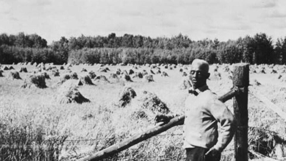 J.D. Edwards pose près d'une clôture. Derrière lui se trouvent un champ et des arbres.