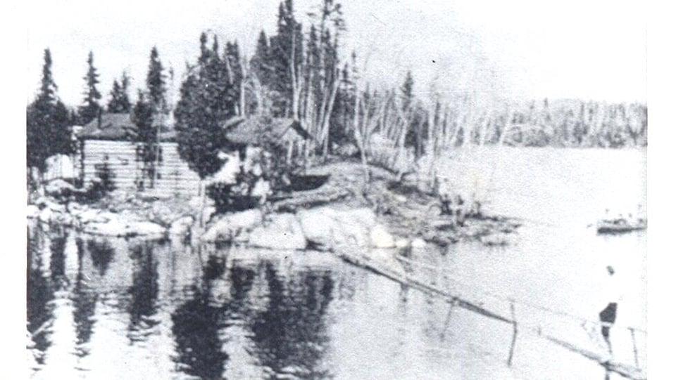 Une photo d'archives d'une maison en bois rond sur un lac au début du 20e siècle.