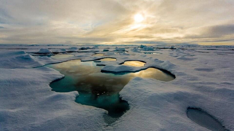 La couverture de glace de l'océan Actique partiellement fondue par endroits.
