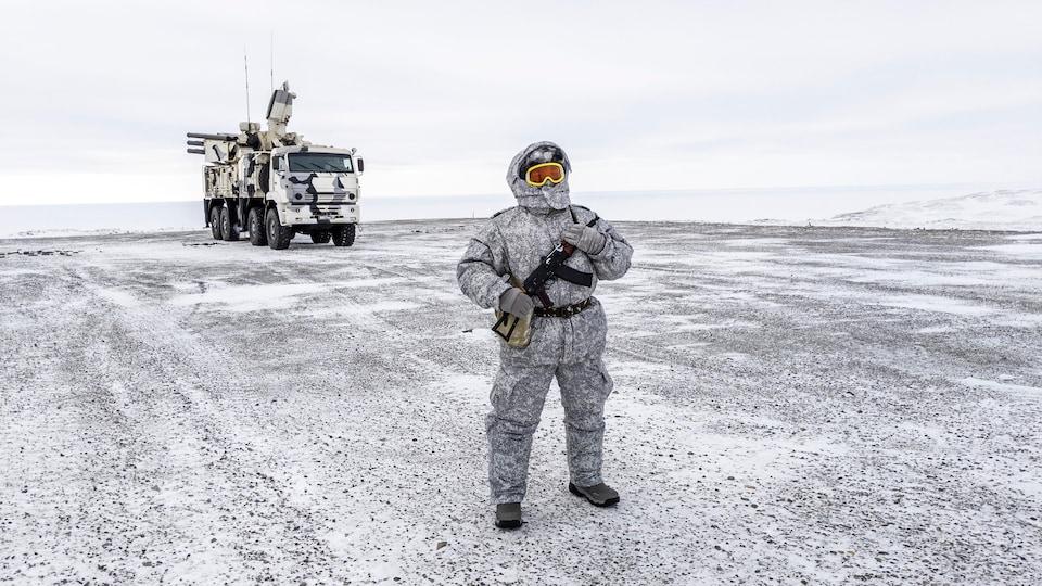 Un soldat en habit hivernal monte la garde.
