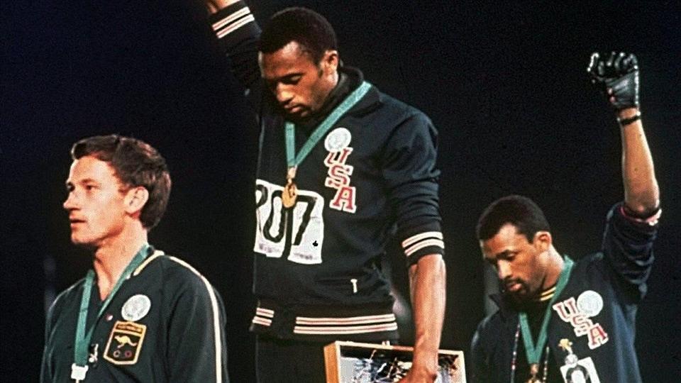 Deux hommes noirs sur un podium lèvent le poing en gardant la tête baissée.