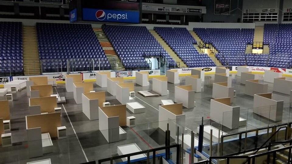 Le centre de l'aréna est occupé par des installations en bois constituées de panneaux de séparation, de lits et de meubles de chevet.