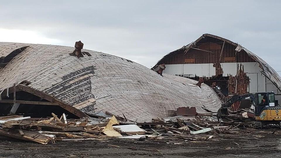 Un travailleur, assis dans la cabine d'une pelle mécanique, s'affaire à démolir l'aréna.