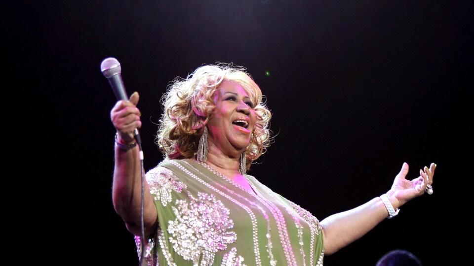 Aretha Franklin écarte les bras, alors qu'elle tient le micro dans sa main droite, et chante, lors d'un concert à New York, en 2012.