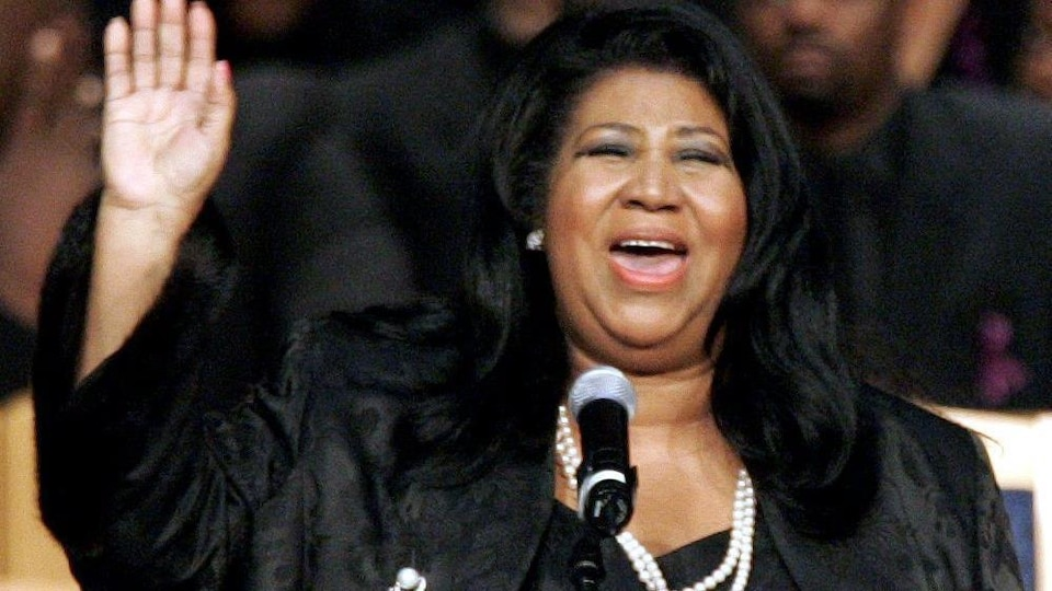 la chanteuse lève sa main et ferme les yeux.
