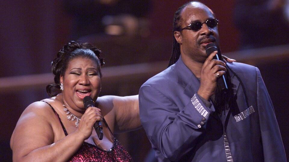 Aretha Franklin tient Stevie Wonder par l'épaule alors que les deux artistes chantent lors d'un concert en 2001 à New York.