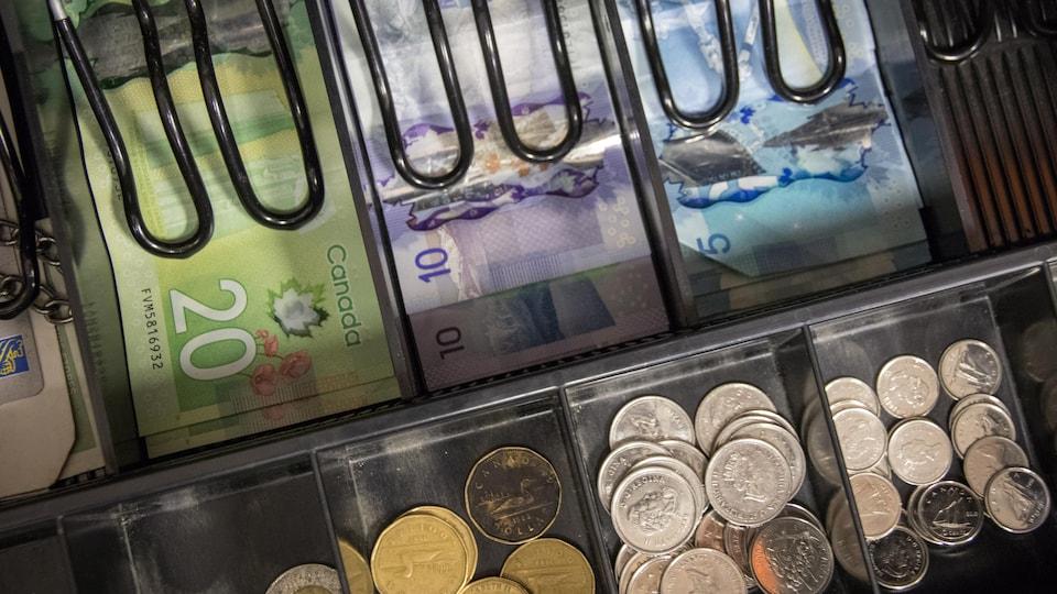 Vue de l'intérieur d'une caisse enregistreuse, remplie de billets de banque et de pièces de monnaie.