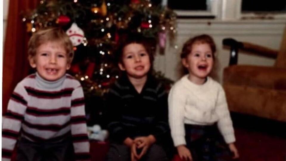 Trois enfants assis devant un sapin de Noël.