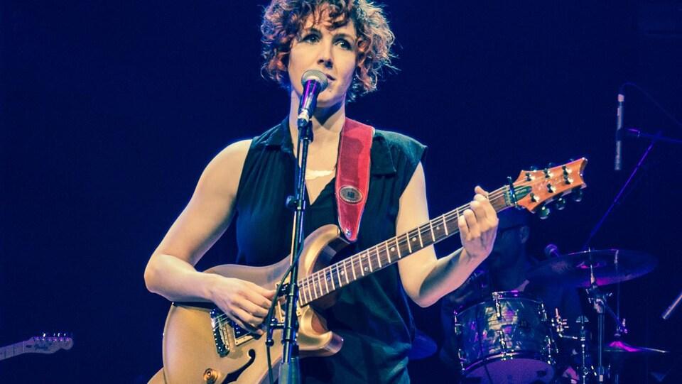 Ariane Jean, sur scène, tenant un guitare et chantant au micro.