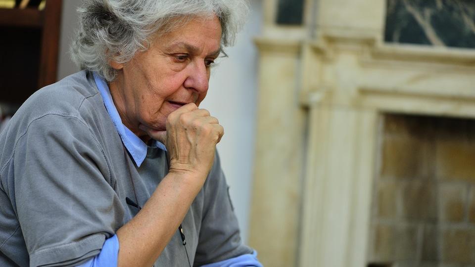 Ariane Mnouchkine, fondatrice du Théâtre du Soleil, regarde vers le sol, tenant son menton dans sa main.
