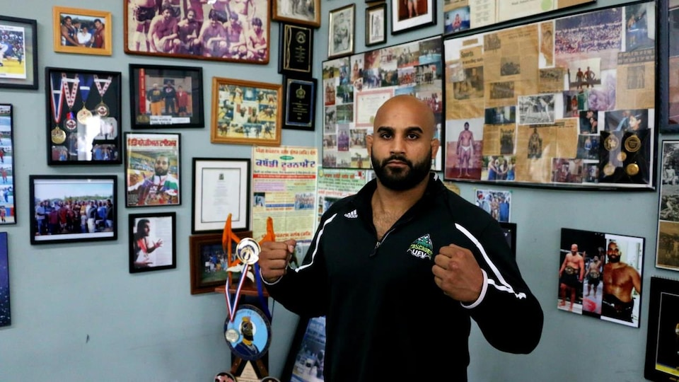 Arjan Bhullar  devant des médailles, des photos et des coupures de journaux illustrant son parcours.