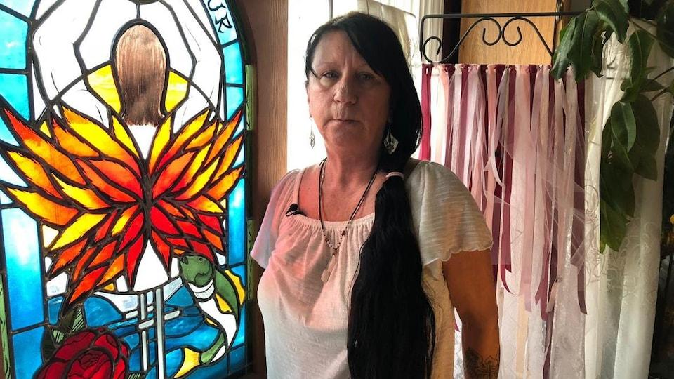 Une femme devant un vitrail.