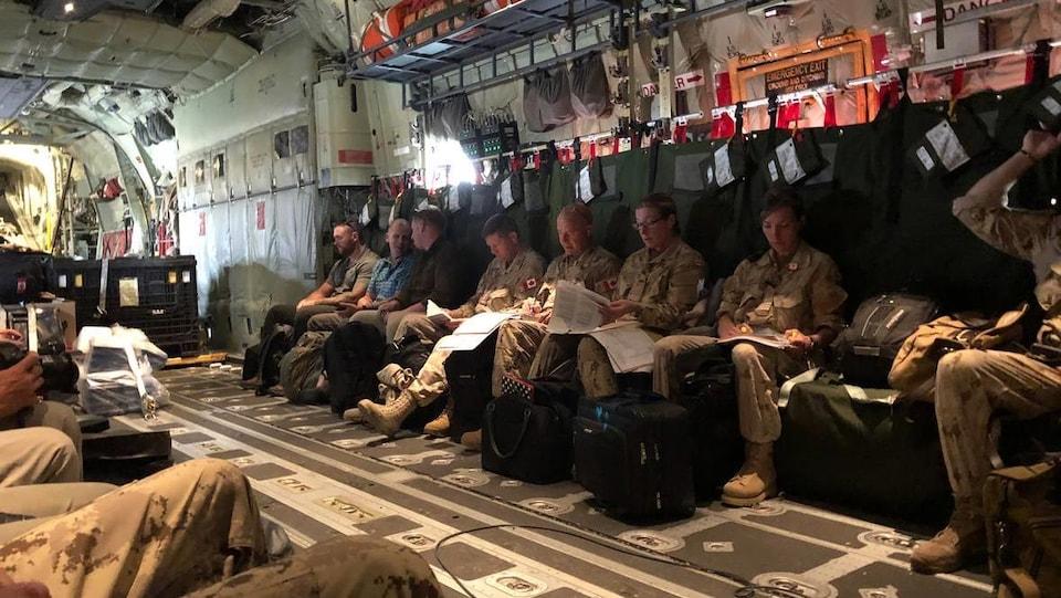 Des soldats canadiens dans un avion de transport.