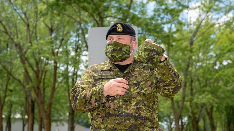 Un militaire porte un masque et en montre un second.