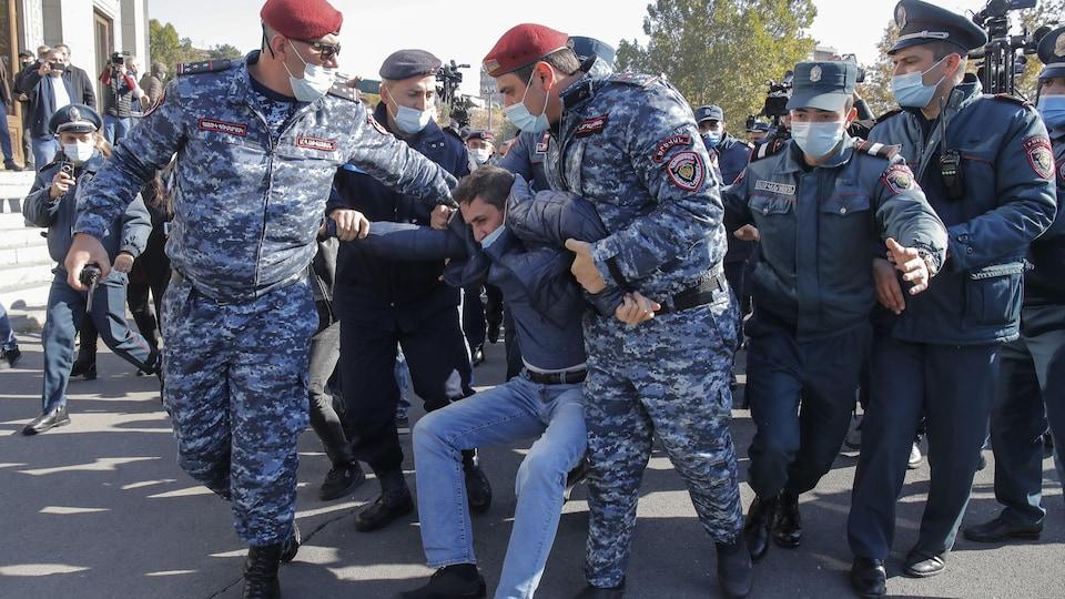 Des hommes en uniforme tirent un manifestant qui résiste à son arrestation.