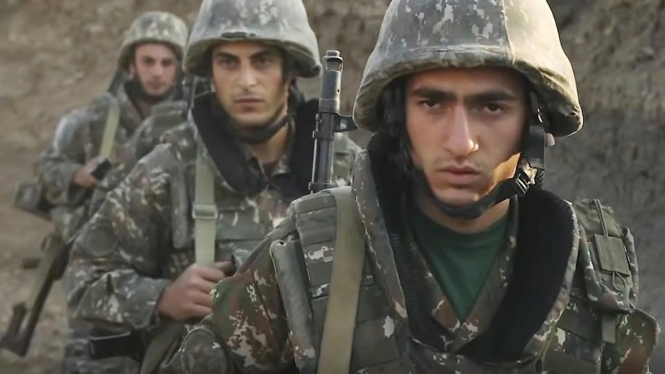 Des militaires marchent dans des tranchées en file.