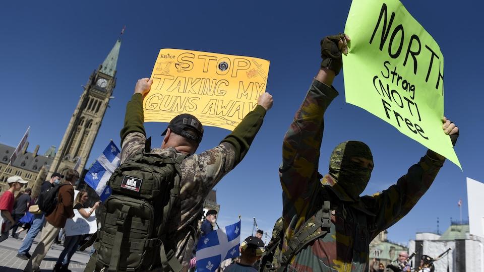 Parmi une foule devant le parlement à Ottawa, des citoyens brandissent des pancartes revendiquant le droit de posséder des armes à feu.