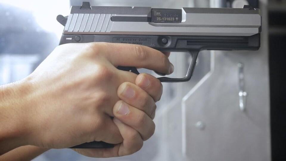 Un gros plan sur une main qui saisit une arme à feu,