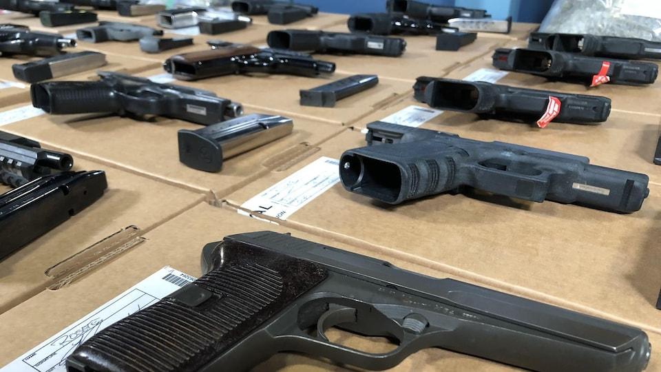 Gros plan sur des armes de poing disposées sur une table.