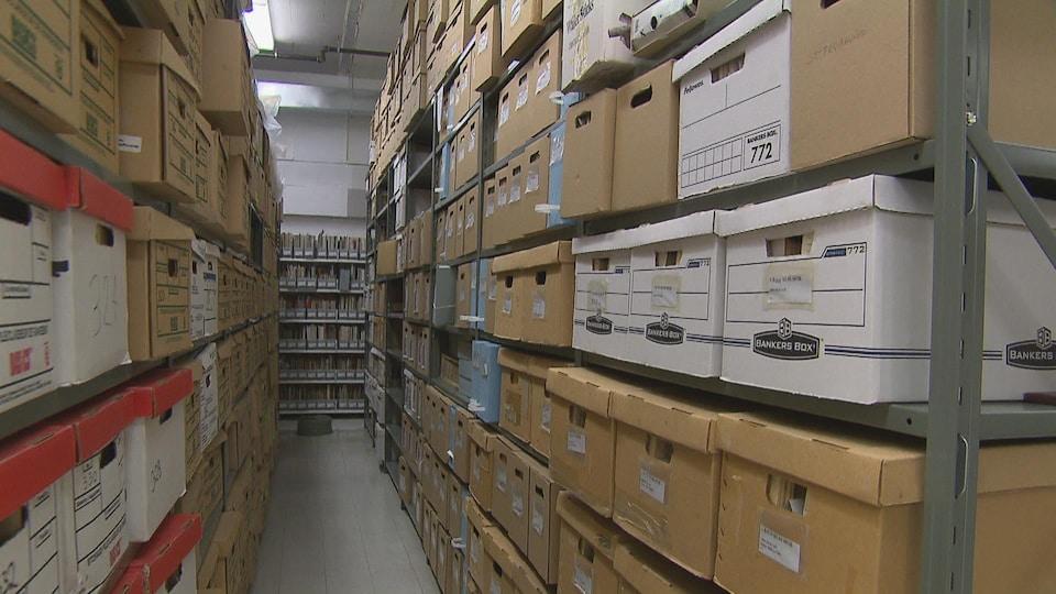 Des boîtes renfermant des archives sont rangées dans des armoires.