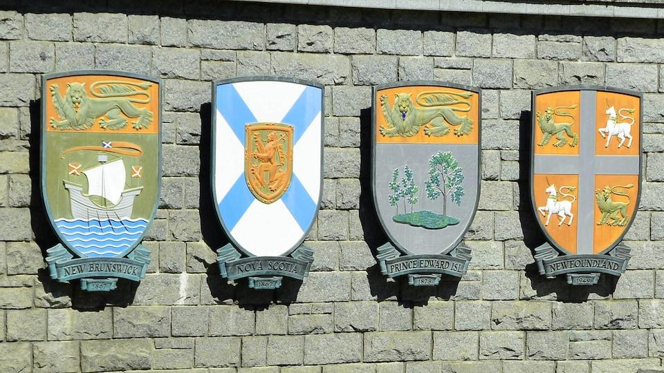 Les armoiries des quatre provinces fixées à un mur de brique.