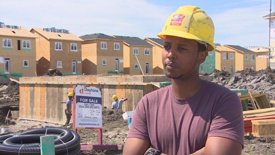 Un homme portant un casque de construction et ayant les bras croisés se tient devant le chantier de construction d'une maison dans un quartier résidentiel.