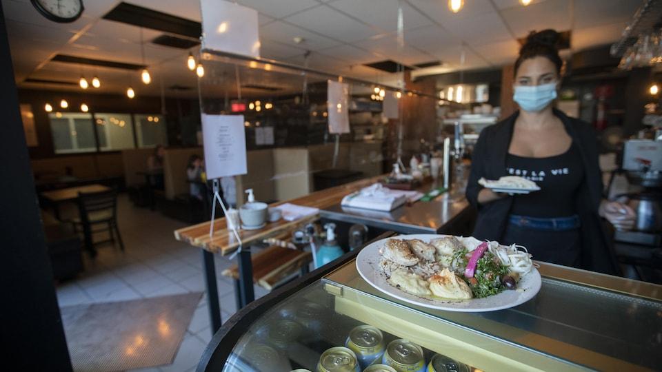 Une jeune femme portant un couvre-visage transporte une assiette contenant de la nourriture.